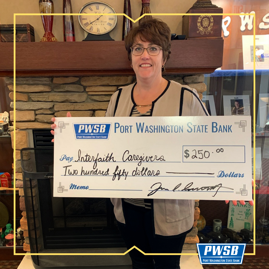 Picture of employee Lois Roeske holding a big fake check.